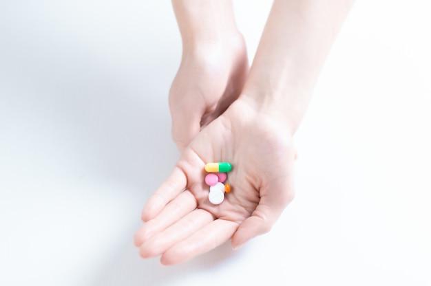 Imagem de comprimidos na palma da mão feminina. o conceito de medicina, saúde, vitaminas. mídia mista