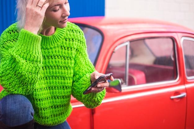 Imagem de conceito colorida de moda com uma garota loira caucasiana em pé perto de um carro antigo vintage vermelho com parede de aço azul. urbano e cores com conceito de tecnologia de viagens de pessoas