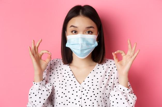 Imagem de conceito de pandemia e estilo de vida de covid de uma linda mulher asiática em máscara facial mostrando seu gesto certo ...