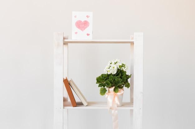 Imagem de coração, livros e planta interna em uma estante