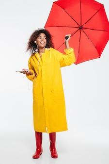 Imagem de corpo inteiro da mulher africana sorridente na capa de chuva se escondendo sob o guarda-chuva e ouvindo música enquanto olhando para longe sobre o branco