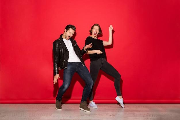 Imagem de corpo inteiro de casal brincalhão punk dançando