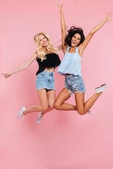 Imagem de corpo inteiro de dois amigos felizes pulando no estúdio