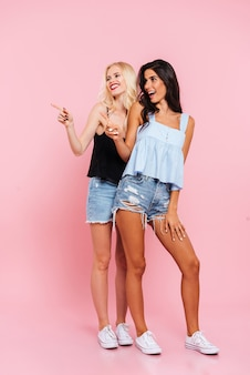Imagem de corpo inteiro de duas mulheres sorridentes em roupas de verão, apontando e olhando para longe sobre rosa
