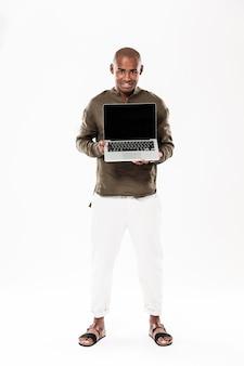 Imagem de corpo inteiro de feliz homem africano mostrando a tela do computador laptop em branco e olhando
