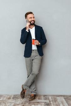 Imagem de corpo inteiro de feliz homem barbudo em roupas de negócios