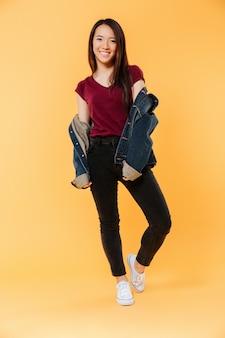 Imagem de corpo inteiro de feliz mulher asiática em jaqueta jeans posando