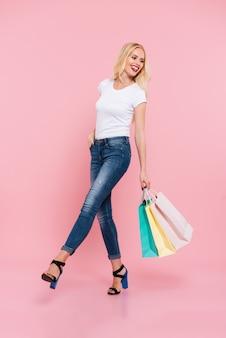 Imagem de corpo inteiro de feliz mulher loira despreocupada andando com pacotes e olhando para trás sobre rosa