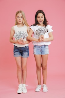 Imagem de corpo inteiro de garotas morenas e loiras encantadas de 8 a 10 anos vestindo roupas casuais e expressando surpresa enquanto seguram muito dinheiro em um dólar, isolado sobre um fundo rosa