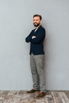 Imagem de corpo inteiro de homem barbudo em roupas de negócios posando com braços cruzados e olhando para a câmera sobre cinza