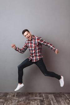 Imagem de corpo inteiro de homem feliz em jeans e camisa gritando enquanto corre e olha
