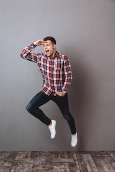 Imagem de corpo inteiro de homem feliz em jeans e camisa, jimping e desviar o olhar com o braço no bolso