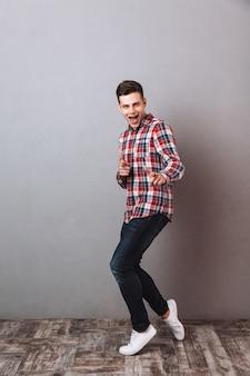 Imagem de corpo inteiro de homem satisfeito em camisa e calça jeans apontando e olhando