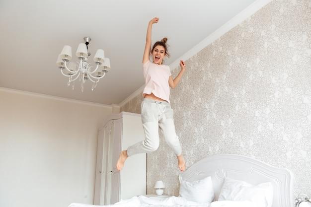 Imagem de corpo inteiro de jovem se divertindo na cama