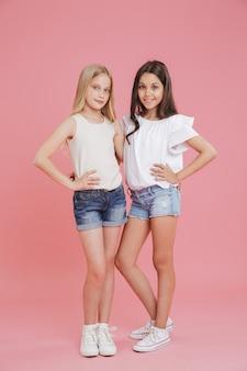 Imagem de corpo inteiro de lindas garotas de 8 a 10 anos vestindo camisetas e shorts jeans, sorrindo e olhando para a câmera enquanto se abraçam, isoladas sobre fundo rosa