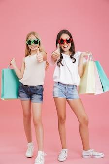 Imagem de corpo inteiro de meninas elegantes morenas e loiras de 8 a 10 anos usando óculos escuros engraçados, segurando sacolas de compras e mostrando os polegares para cima, isolado sobre um fundo rosa
