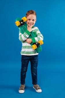 Imagem de corpo inteiro de menino sorridente, abraçando o skate