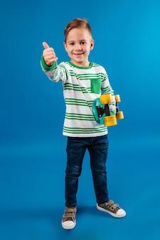 Imagem de corpo inteiro de menino sorridente segurando o skate