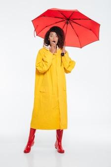 Imagem de corpo inteiro de mulher africana chocada em capa de chuva