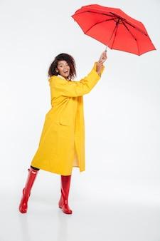 Imagem de corpo inteiro de mulher africana despreocupada em capa de chuva