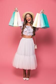 Imagem de corpo inteiro de mulher alegre usando chapéu de palha e saia fofa gritando e segurando pacotes de compras de papel colorido