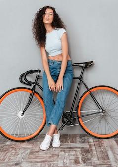 Imagem de corpo inteiro de mulher bonita encaracolada posando com bicicleta e olhando para a câmera sobre fundo cinza