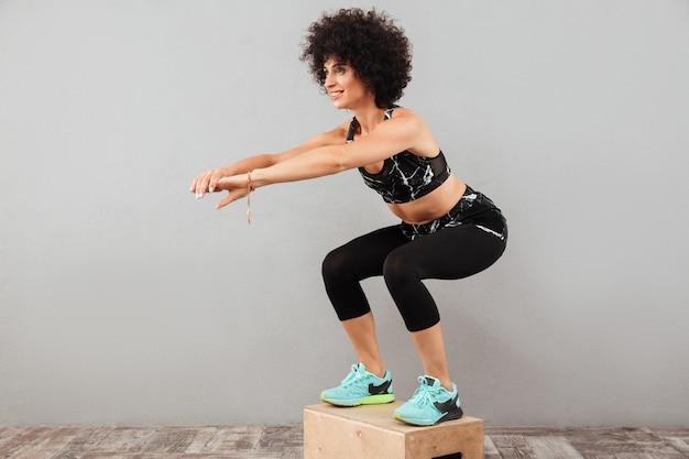 Imagem de corpo inteiro de mulher de esportes fazendo exrecise na caixa