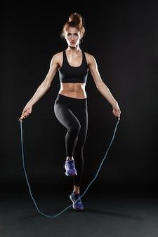 Imagem de corpo inteiro de mulher fitness pulando com corda de pular