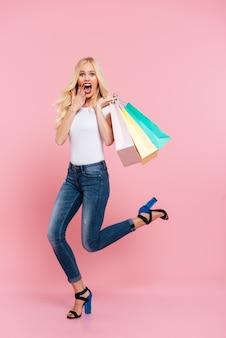 Imagem de corpo inteiro de mulher loira chocada, movendo-se com pacotes e olhando para a câmera sobre rosa