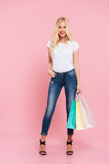 Imagem de corpo inteiro de mulher loira feliz posando com pacotes e segurando o braço no bolso enquanto olha para a câmera sobre rosa