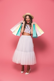Imagem de corpo inteiro de mulher viciada em compras usando chapéu de palha e saia fofa sorrindo e segurando sacolas de papel colorido