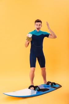 Imagem de corpo inteiro de surfe feliz surfista em roupa de mergulho usando prancha de surf, segurando um cocktail e olhando para a câmera