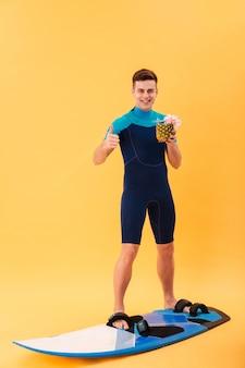 Imagem de corpo inteiro de surfista feliz em roupa de mergulho usando prancha de surf, mantendo o cocktail e aparecendo o polegar
