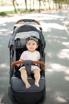 Imagem de corpo inteiro de um bebê asiático feliz sentado em um carrinho. fundo desfocado de um jardim público com sombra