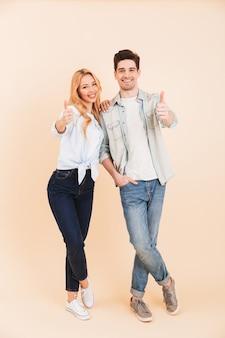 Imagem de corpo inteiro de um casal satisfeito, um homem e uma mulher de 20 anos em roupas jeans, sorrindo e mostrando os polegares para cima, isolada sobre uma parede bege