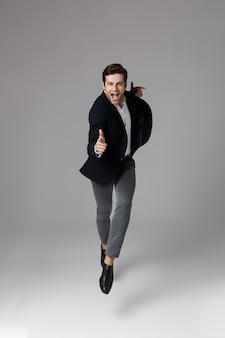 Imagem de corpo inteiro de um empresário atraente de 30 anos em um terno formal apontando o dedo para você, isolada sobre uma parede cinza