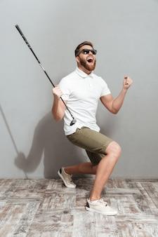 Imagem de corpo inteiro de um jogador de golfe gritando em óculos de sol