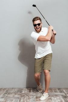Imagem de corpo inteiro de um jogador de golfe legal em óculos de sol