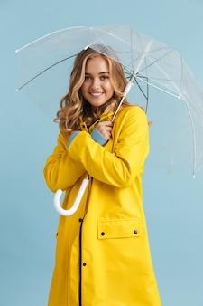Imagem de corpo inteiro de uma encantadora mulher de 20 anos vestindo uma capa de chuva amarela sob um guarda-chuva transparente
