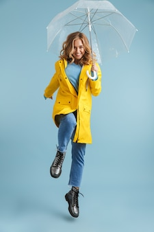 Imagem de corpo inteiro de uma jovem de 20 anos vestindo uma capa de chuva amarela sob um guarda-chuva transparente