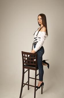 Imagem de corpo inteiro de uma jovem morena com uma blusa branca, jeans e um arnês posando na cadeira e olhando para a frente sobre a superfície bege