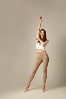Imagem de corpo inteiro de uma jovem morena de blusa curta e calça skinny posando e olhando para a frente sobre a superfície bege