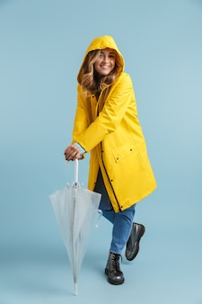 Imagem de corpo inteiro de uma mulher caucasiana de 20 anos usando capa de chuva amarela e guarda-chuva transparente
