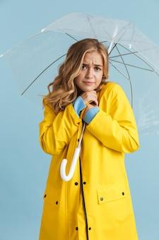 Imagem de corpo inteiro de uma mulher elegante de 20 anos vestindo uma capa de chuva amarela sob um guarda-chuva transparente