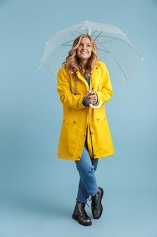 Imagem de corpo inteiro de uma mulher europeia de 20 anos vestindo uma capa de chuva amarela sob um guarda-chuva transparente