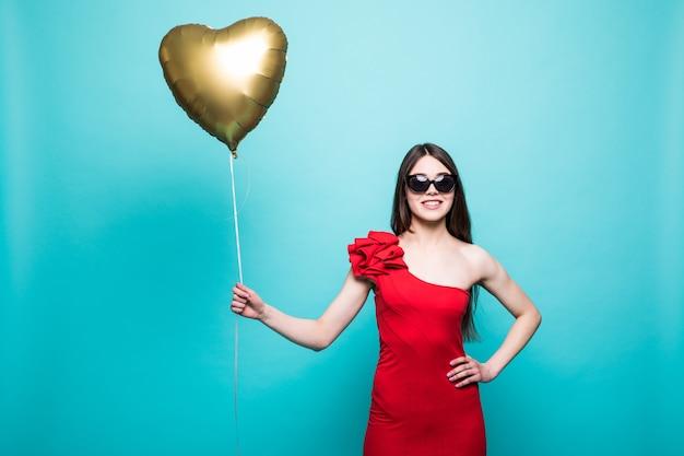 Imagem de corpo inteiro de uma mulher linda em um traje vermelho chique posando com um balão em forma de coração, isolado sobre uma parede verde