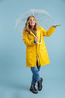 Imagem de corpo inteiro de uma mulher loira de 20 anos vestindo uma capa de chuva amarela sob um guarda-chuva transparente
