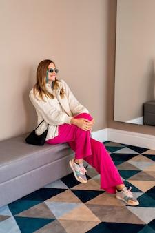 Imagem de corpo inteiro de uma mulher loira na moda posando em um hotel de luxo, usando uma roupa casual colorida e aconchegante