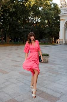Imagem de corpo inteiro de uma mulher muito romântica em vestido rosa posando ao ar livre na velha cidade europeia.