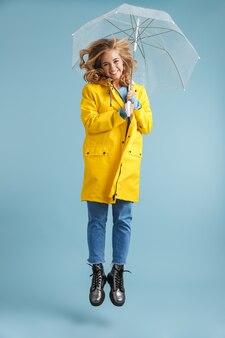 Imagem de corpo inteiro de uma mulher positiva de 20 anos, com capa de chuva amarela, sob um guarda-chuva transparente